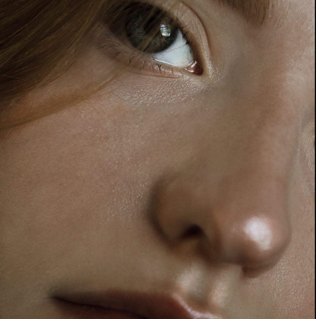 close-up of a young woman with radiant glass skin